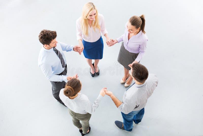Gens d'affaires tenant des mains pour former un cercle photo stock
