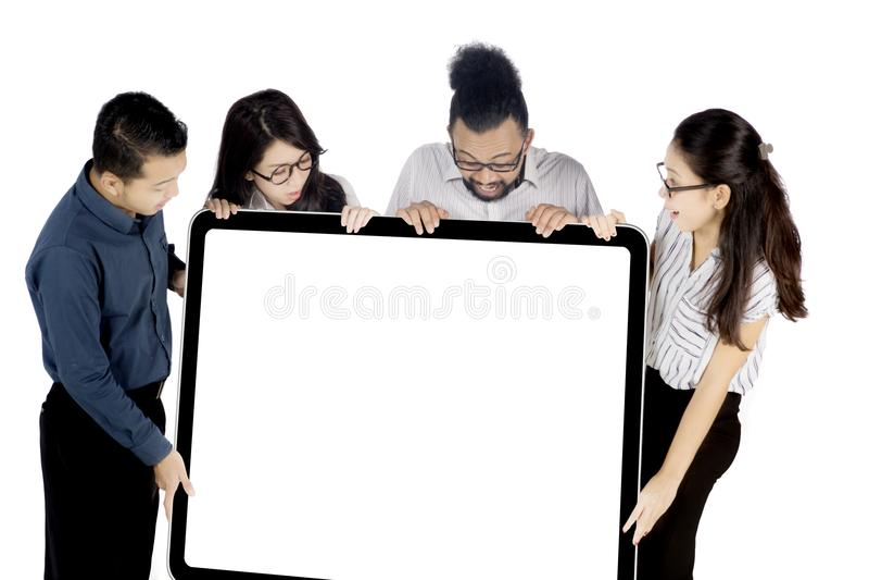 Gens d'affaires tenant le tableau blanc sur le studio photographie stock libre de droits