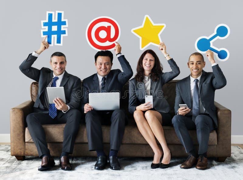 Gens d'affaires tenant les icônes sociales de réseau photos stock