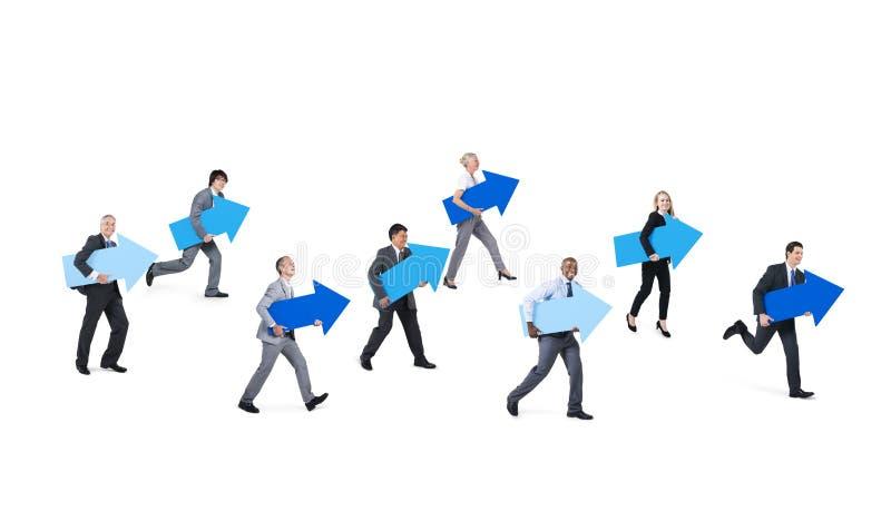 Gens d'affaires tenant les signes bleus de flèche photographie stock