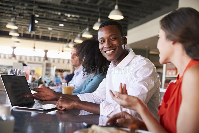 Gens d'affaires travaillant au compteur dans le café photo stock
