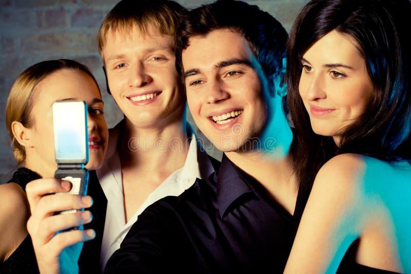 Gens de sourire de embrassement de jeunes prenant la photographie par le portable images stock