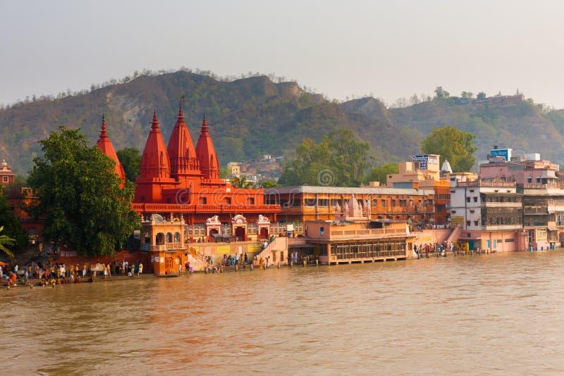 Gens rouges de fleuve de Ganges de temple se baignant photos stock