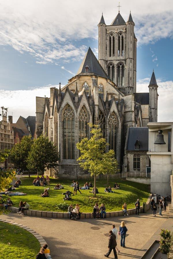 Gent, Bélgica - 10 26 2019: Igreja de São Nicolau Sint-Niklaaskerk uma bela vista do parque com algumas pessoas e com o grande se imagens de stock royalty free