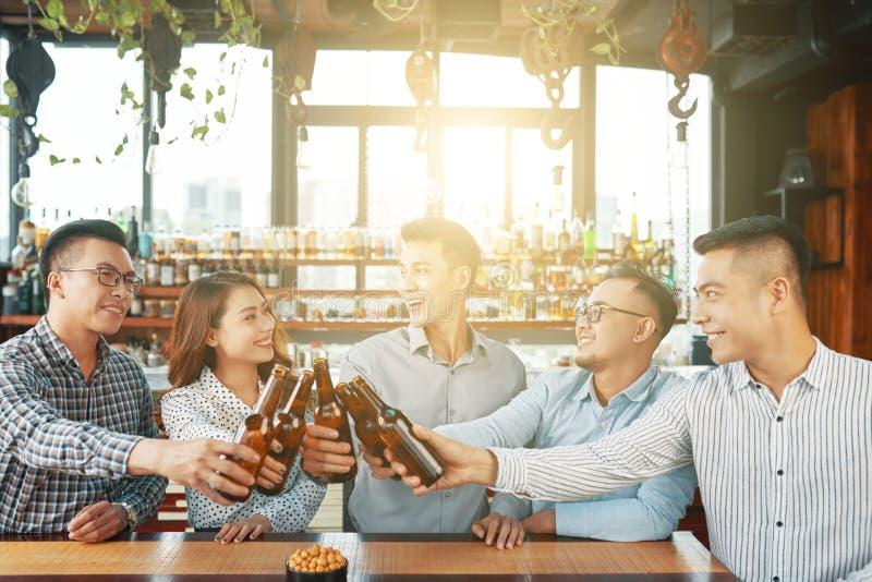 Gente étnica alegre que celebra en barra imagen de archivo