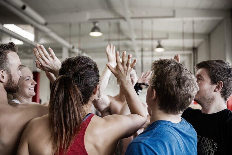 Gente acertada que da el alto cinco el uno al otro en gimnasio imagenes de archivo