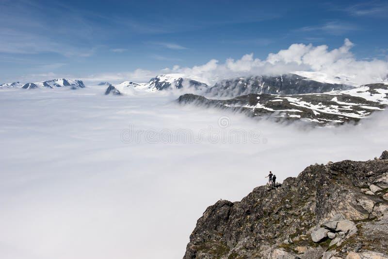 Gente al borde del pico de montaña sobre las nubes, visión desde la montaña Dalsnibba a Geirange imagen de archivo