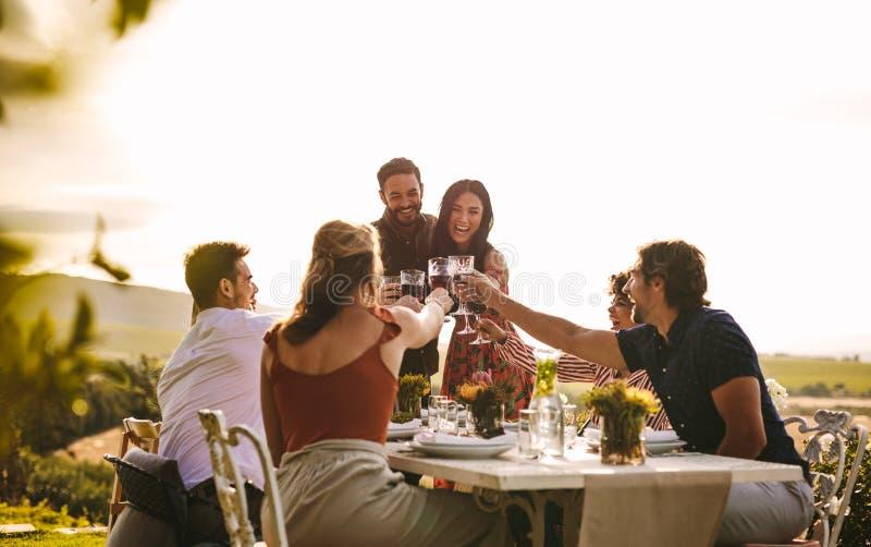 Gente alegre que celebra con las bebidas en el partido imagenes de archivo