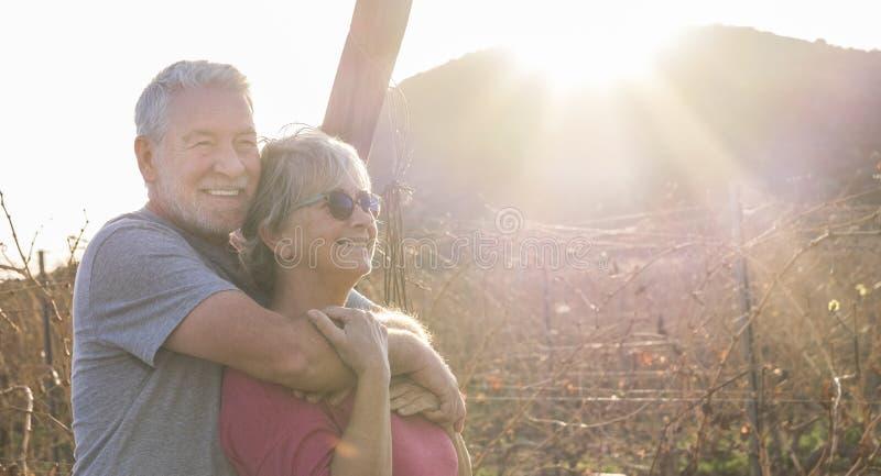 Gente allegra e sana coppia di anziani caucasici uomini e donne in attività ricreative all'aperto abbracciando e fotografia stock