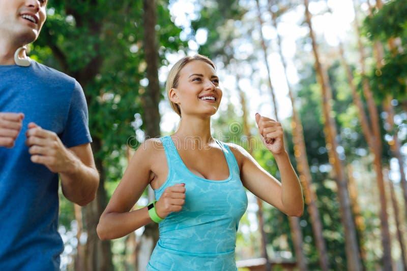 Gente apta del positivo feliz que corre al aire libre junto foto de archivo