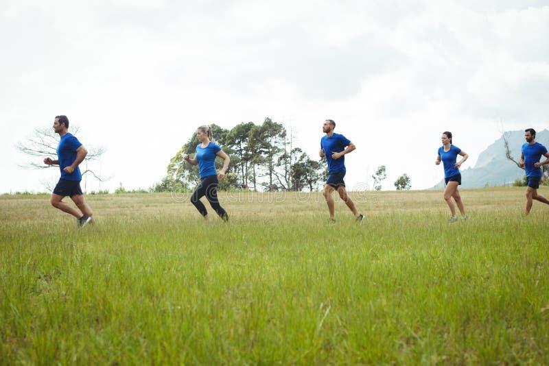 Gente apta que corre en campo de bota foto de archivo