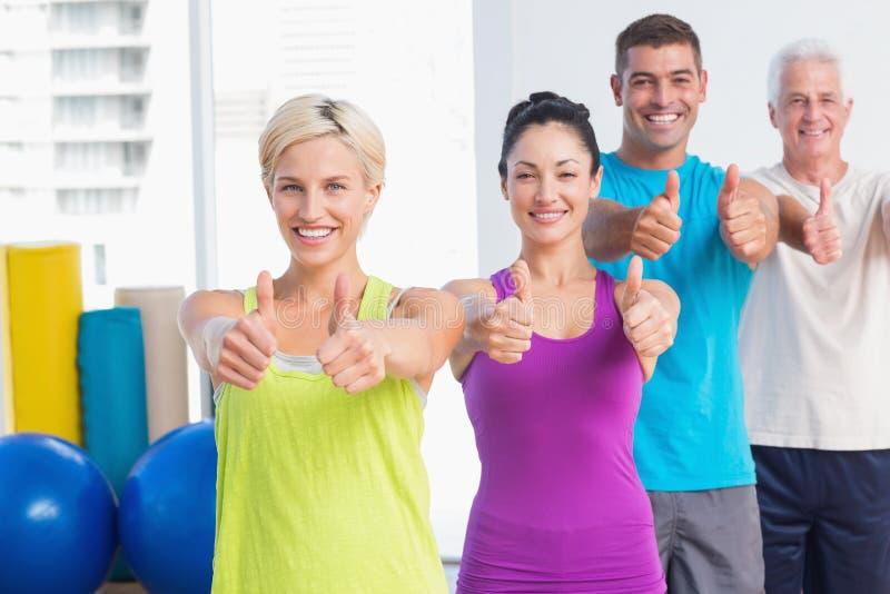 Gente apta que gesticula los pulgares para arriba en el gimnasio imagenes de archivo