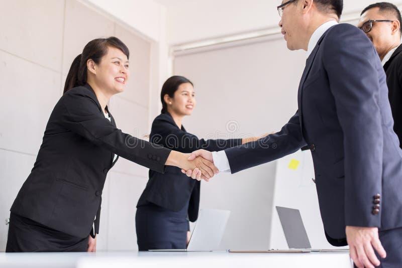 Gente asiática del equipo del negocio que sacude las manos después de acabar para arriba la reunión en la sala de conferencias fotografía de archivo libre de regalías
