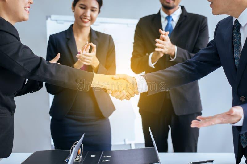 Gente asiática del equipo del negocio que sacude las manos después de acabar para arriba la reunión en la sala de conferencias imagen de archivo libre de regalías