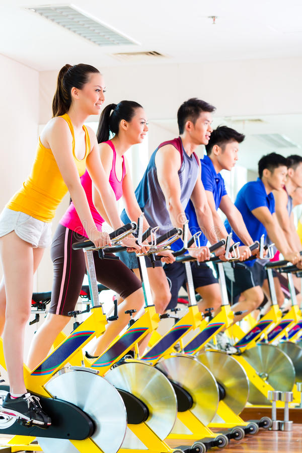 Gente asiática en el entrenamiento de giro de la bici en el gimnasio de la aptitud fotografía de archivo libre de regalías
