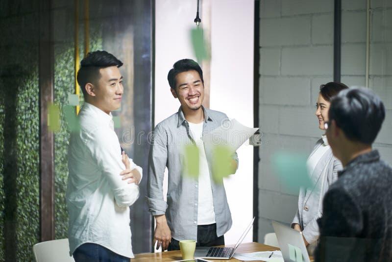 Gente asiática joven del equipo del negocio que se encuentra en oficina fotos de archivo