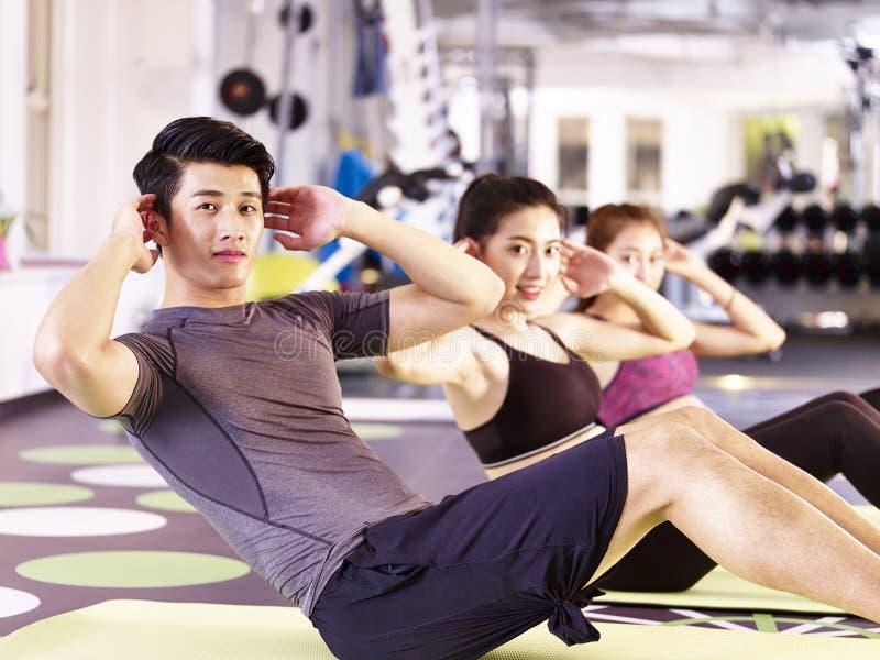 Gente asiática joven que ejercita en gimnasio imagen de archivo libre de regalías