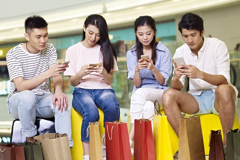 Gente asiática joven que juega con los teléfonos móviles foto de archivo libre de regalías