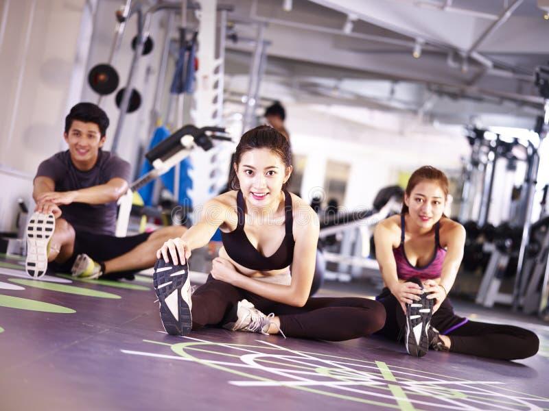 Gente asiática joven que se resuelve en gimnasio foto de archivo