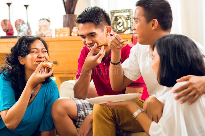 Gente asiática que come la pizza en el partido imagen de archivo