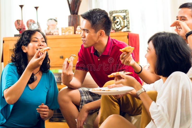 Gente asiática que come la pizza en el partido imagenes de archivo
