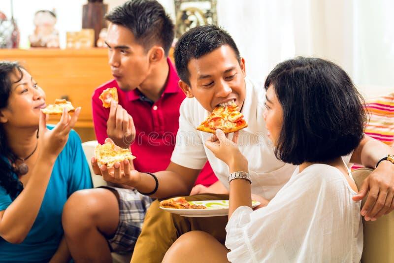Gente asiática que come la pizza en el partido foto de archivo libre de regalías