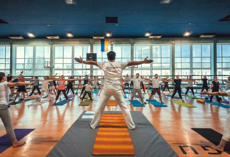 Gente attiva che esegue insieme yoga, facente gli esercizi e preparantesi il giorno internazionale di yoga immagine stock libera da diritti