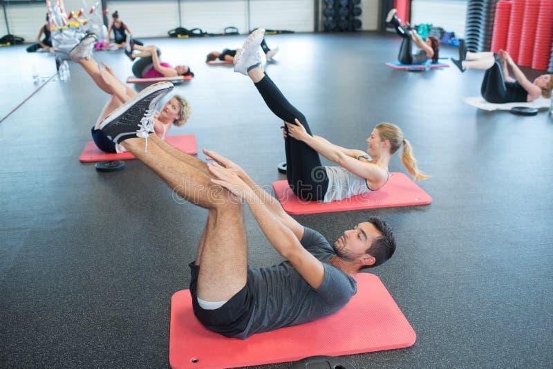 Gente attiva del ritratto che fa gamba che allunga sulla stuoia di esercizio fotografie stock