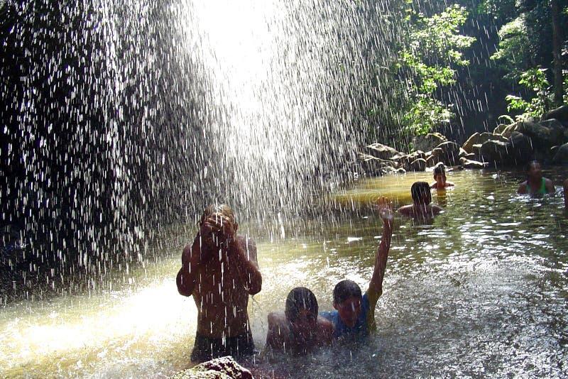 Gente bajo la cascada fotos de archivo libres de regalías