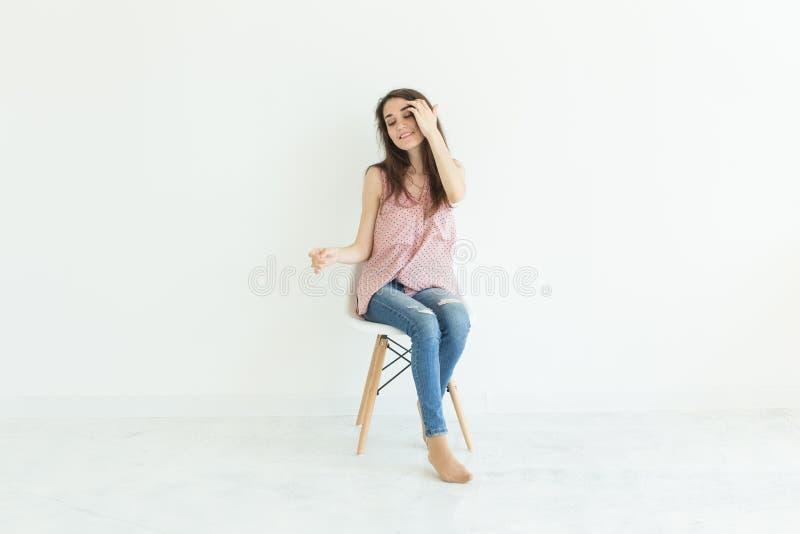 Gente, belleza y concepto de la moda - mujer morena joven que presenta en la silla aislada en el fondo blanco con el espacio de l fotografía de archivo