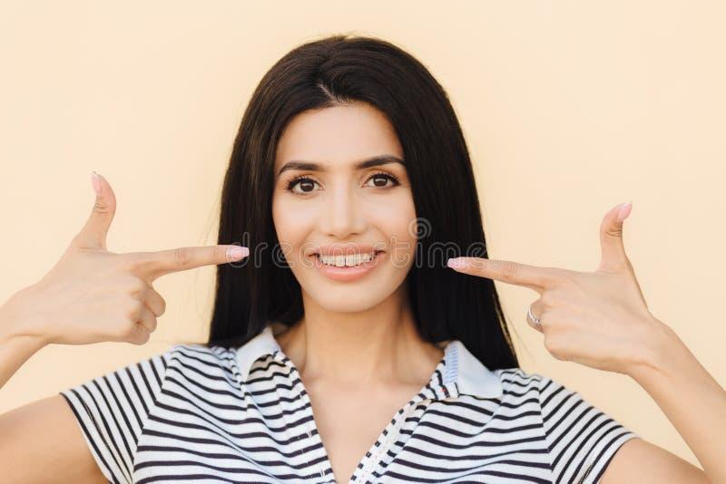 Gente, belleza y concepto de la publicidad La mujer joven morena con sonrisa apacible, indica en la boca con sonrisa amplia, tien foto de archivo libre de regalías