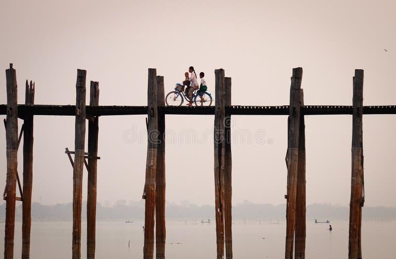 Gente biking en el puente en Mandalay, Myanmar imagen de archivo libre de regalías