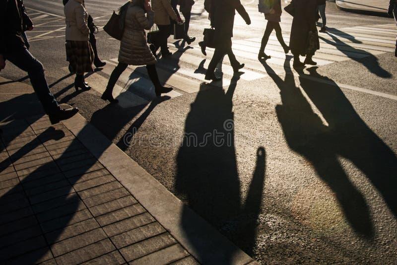 Gente borrosa y sus sombras en la travesía fotos de archivo