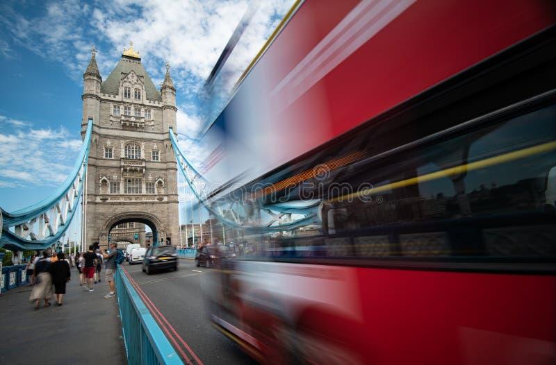 Gente caminando y autobús tradicional rojo en Londres cruzando el famoso puente de la Torre de Londres fotos de archivo libres de regalías
