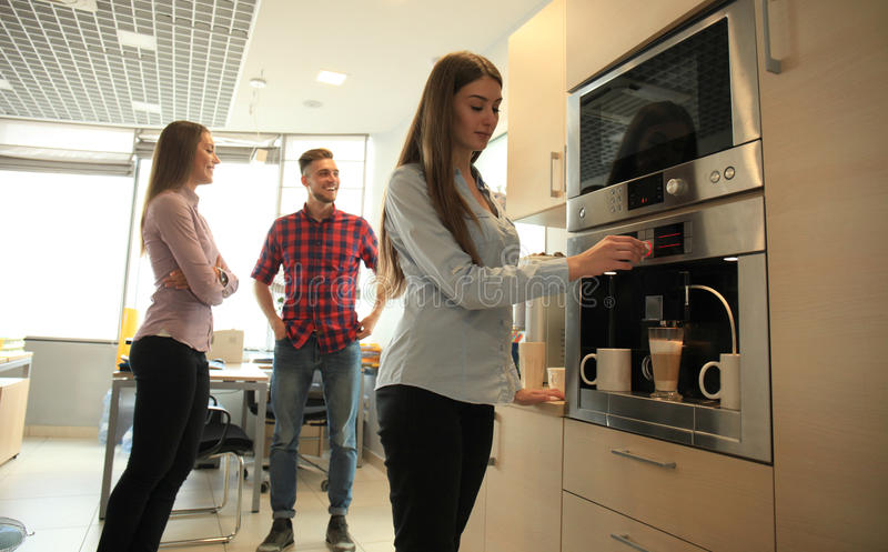Gente casual de la oficina que habla por el fabricante de café fotografía de archivo