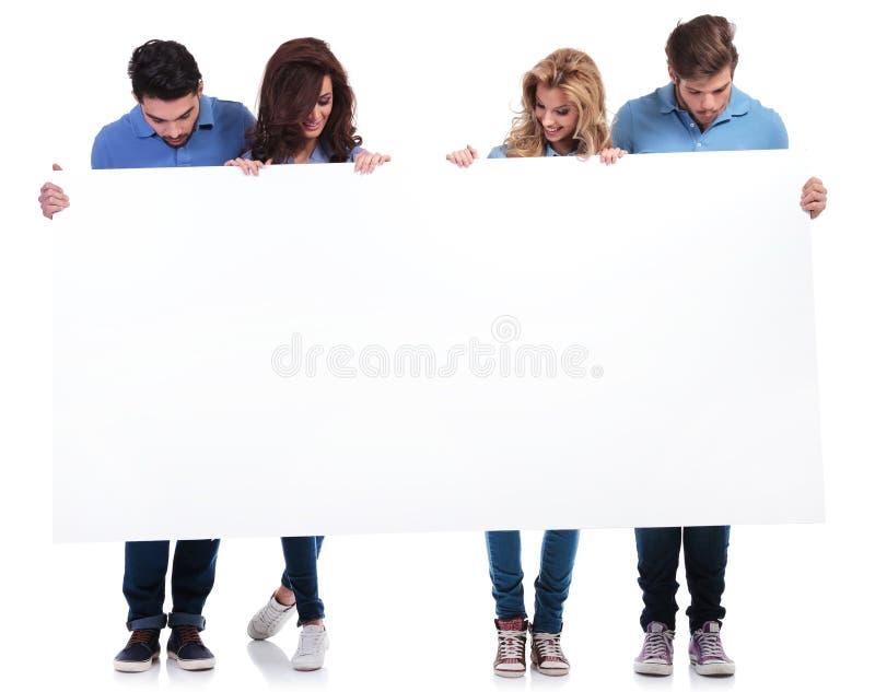 Gente casual que lleva a cabo y que mira a un tablero en blanco fotos de archivo