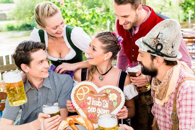 Gente con el corazón del pan de jengibre en jardín de la cerveza imágenes de archivo libres de regalías