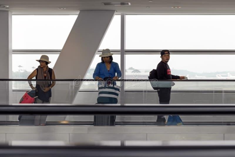 Gente con equipaje en el aeropuerto en una cinta móvil del pasajero fotos de archivo libres de regalías