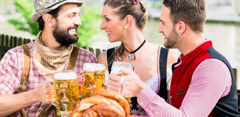 Gente con la cerveza y el pretzel en el mesón de Bavaian imagen de archivo