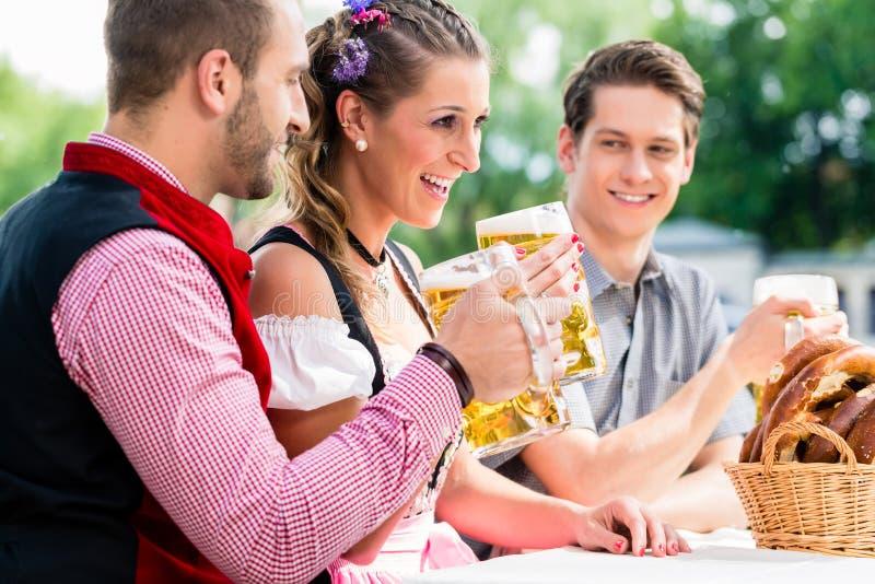 Gente con la cerveza y el pretzel en el mesón de Bavaian imagen de archivo libre de regalías