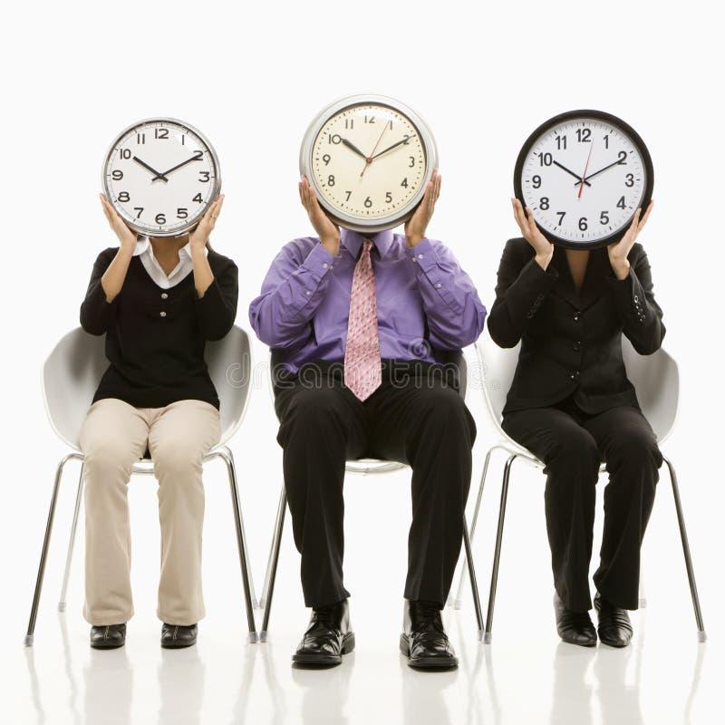 Gente con las caras de reloj fotografía de archivo