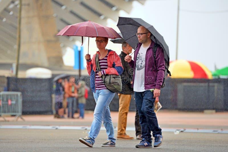 Gente con los paraguas, debajo de la lluvia en el sonido 2014 de Heineken Primavera foto de archivo