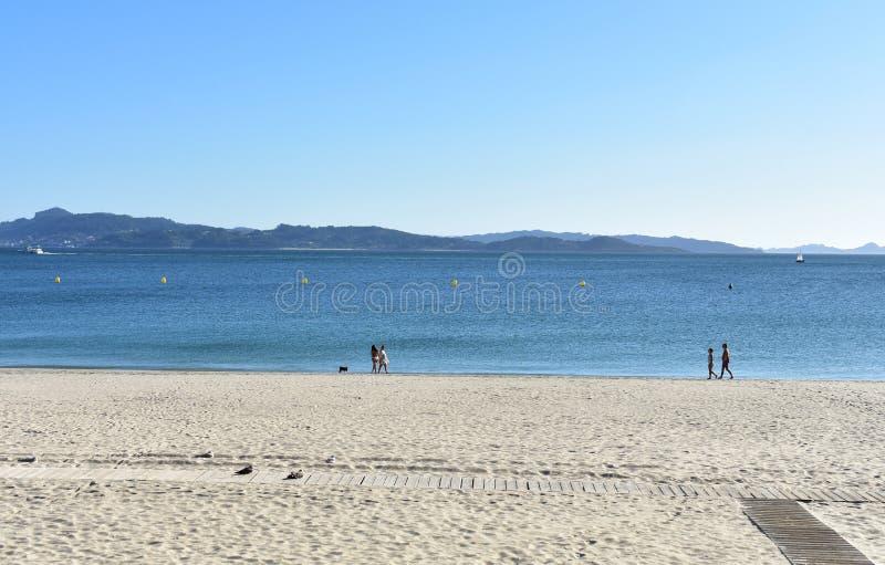 Gente con los perros que caminan en la playa Mar azul con los barcos, cielo claro, día soleado Sanxenxo, Galicia, España imagen de archivo libre de regalías
