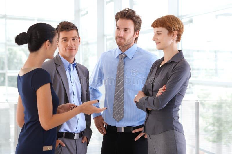 Gente corporativa che chiacchiera all'ingresso dell'ufficio di affari immagini stock libere da diritti