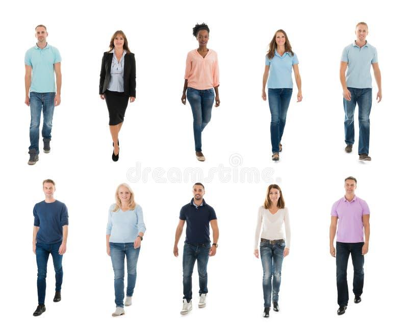 Gente creativa che cammina sopra il fondo bianco immagini stock
