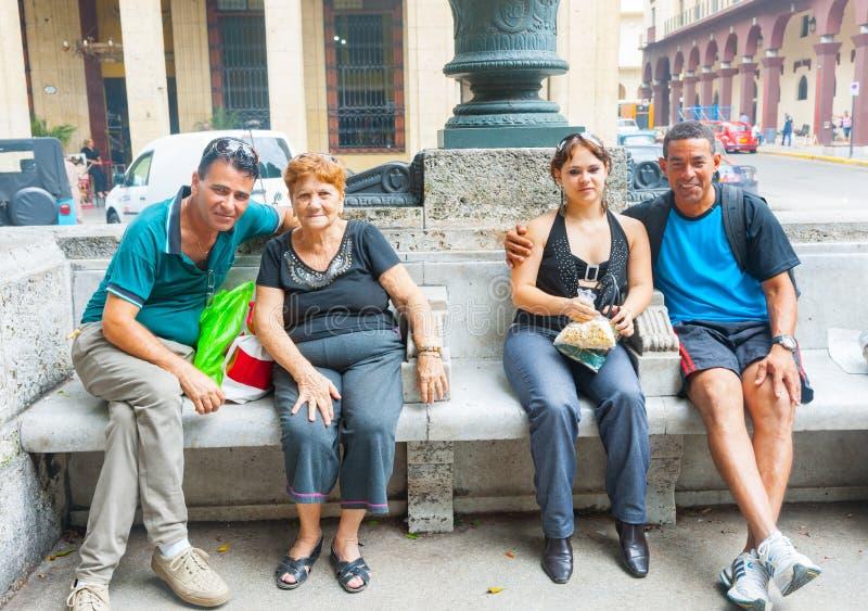 Gente cubana auténtica que se relaja en el banco de la ciudad imagenes de archivo