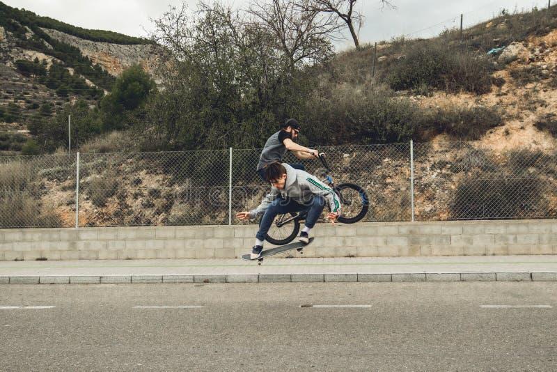 Gente de jóvenes con el monopatín y la bici del bmx Concepto urbano extremo de los deportes fotografía de archivo libre de regalías