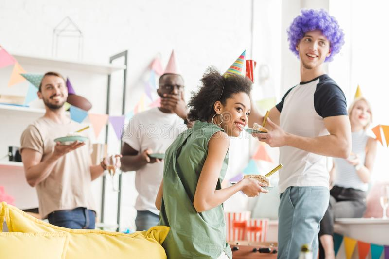 Gente de jóvenes en sombreros del partido que celebra cumpleaños con las bebidas fotografía de archivo libre de regalías