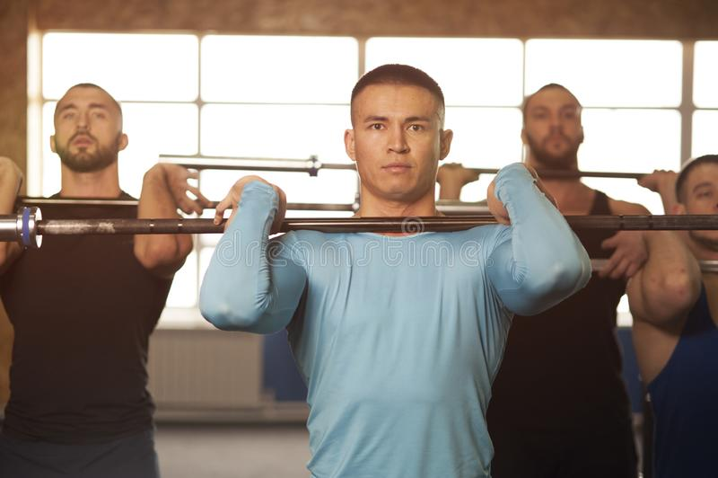 Gente de j?venes en el entrenamiento del gimnasio con los Barbells foto de archivo libre de regalías