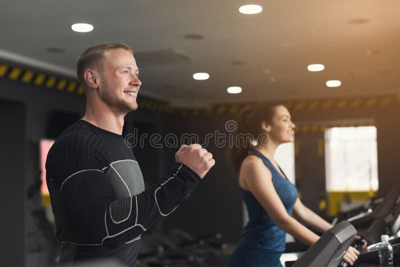 Gente de la aptitud que entrena en gimnasio en las ruedas de ardilla imagen de archivo